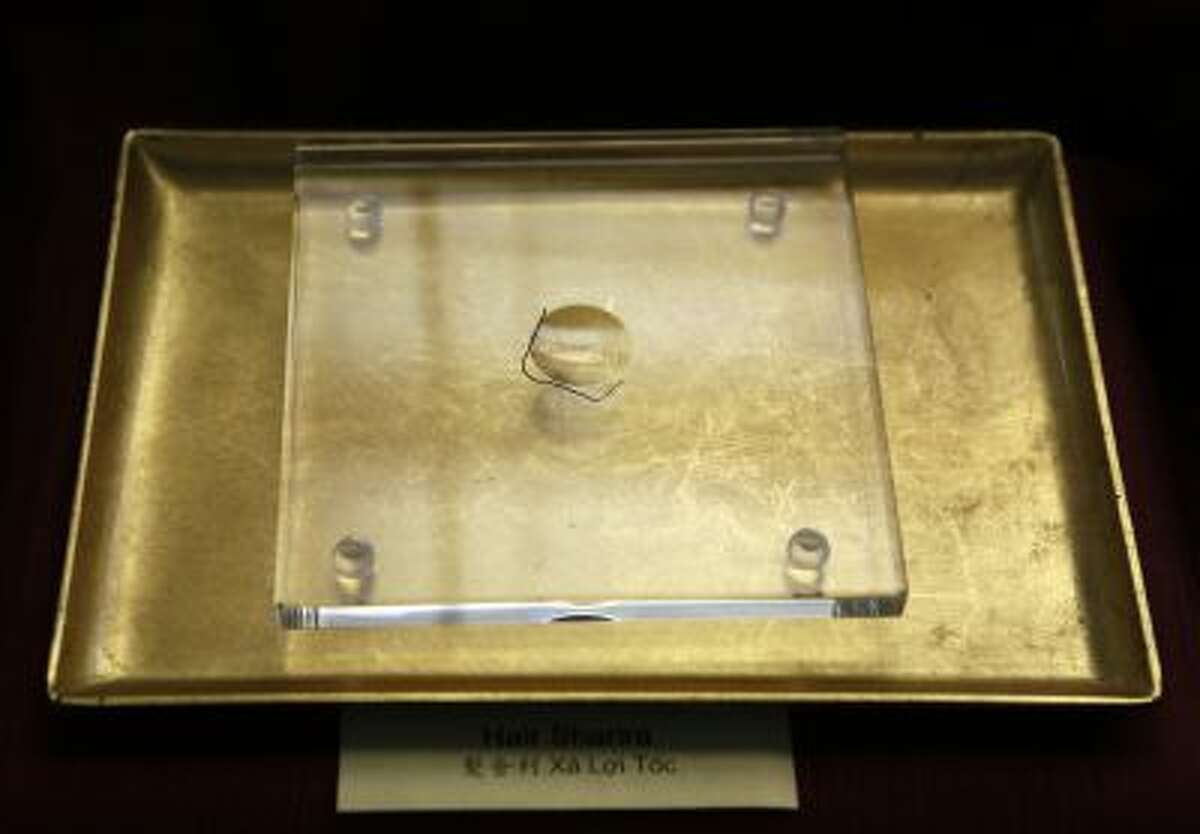 In this Sept. 18, 2013 photo, a single hair believed to have come from Buddha's head is part of the relics displayed at the Lu Mountain Temple in Rosemead, Calif. The temple has become a repository for the colorful crystals and a tooth that are believed to have come from the body of the Buddha himself.