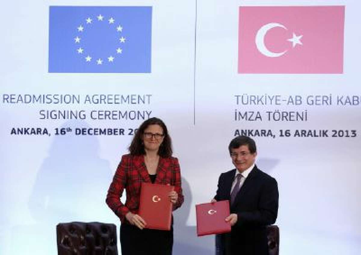 EU Home Affairs Commissioner Cecilia Malmstrom, left, and Turkey's Foreign Minister Ahmet Davutoglu show the agreements they have signed in Ankara, Turkey, Monday, Dec. 16, 2013.