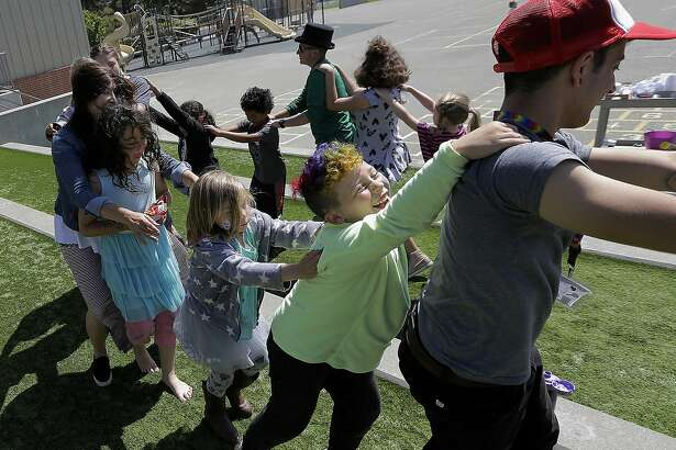 In this Tuesday, July 11, 2017 photo, campers and camp counselors dance at the Bay Area Rainbow Day Camp in El Cerrito, Calif. Organizers say the camp gives kids a safe, fun place to be themselves. The camp's enrollment has tripled since it opened in 2015, and plans are underway to open a branch next summer in Colorado. (AP Photo/Jeff Chiu)
