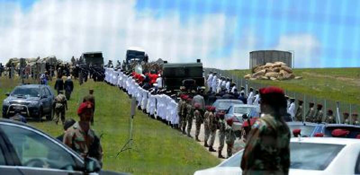 Former South African President Nelson Mandela's casket is taken by military gun carriage to his burial place following his funeral service in Qunu, South Africa, Sunday, Dec. 15, 2013.
