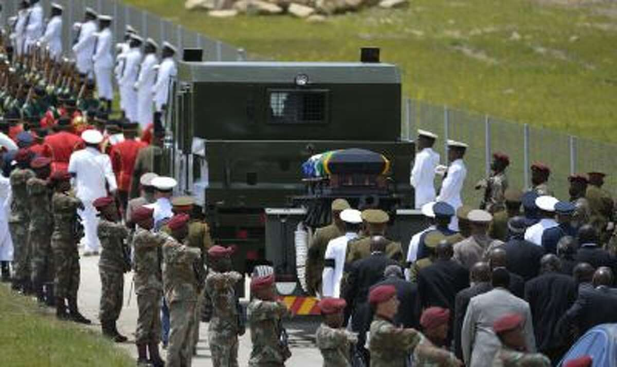 Former South African President Nelson Mandela's casket is take by military gun carriage to his burial place following his funeral service in Qunu, South Africa, Sunday, Dec. 15, 2013.