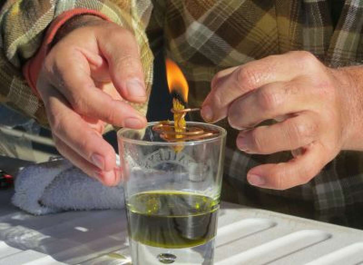 In this Oct. 5, 2013 photo, Derek Cross, a chef who specializes in cooking with hemp, demonstrates the burning properties of hemp oil, which he touts as a digestible bio fuel, during the first known harvest of industrial hemp in the U.S. since the 1950s, at a farm in Springfield, Colo.