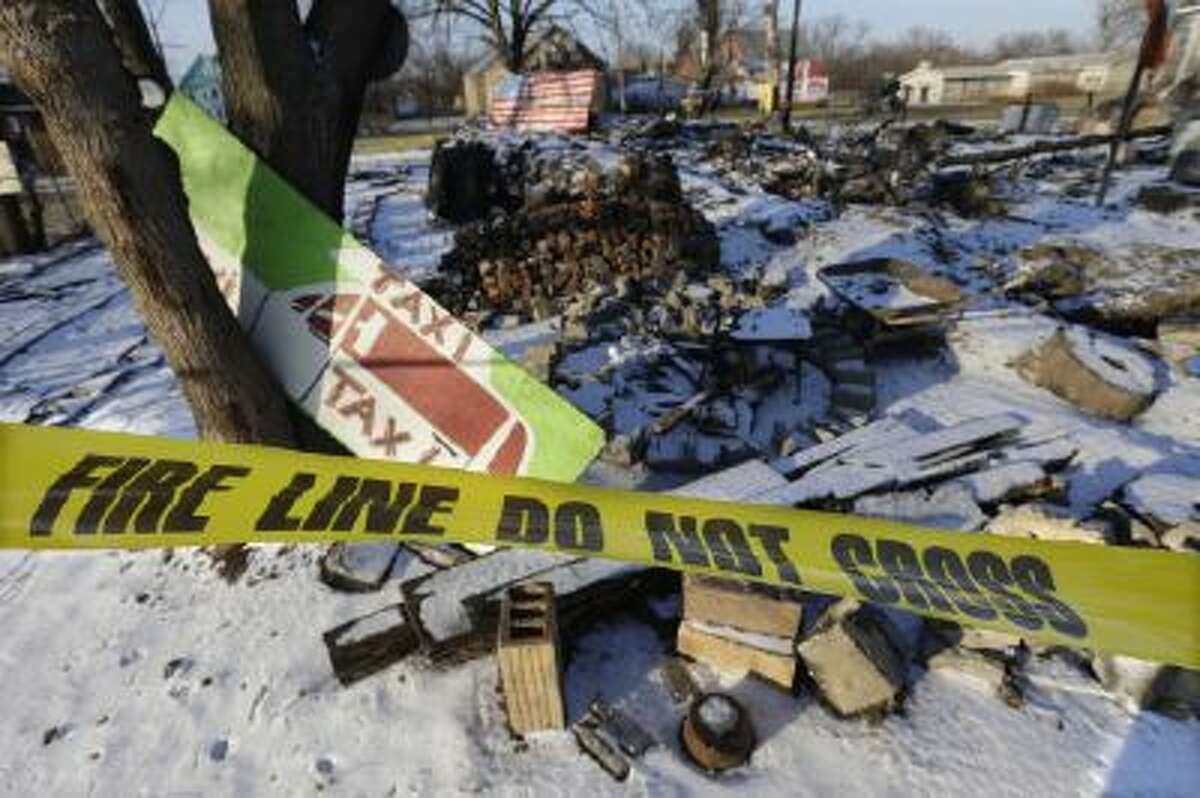 In a photo from Tuesday, Dec. 10, 2013 at the Heidelberg Project in Detroit, fire tape is seen surrounding the aftermath of the fire at the House of Soul.