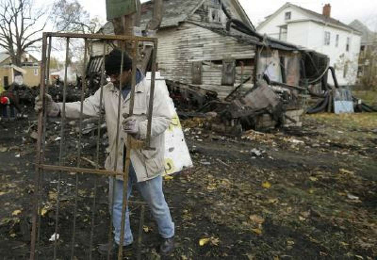 In a photo from Nov. 12, 2013, artist Tyree Guyton moves a metal door from his House of Soul which was destroyed in a fire in Detroit. It?s the second fire in the past few weeks at the unofficial sculpture park.
