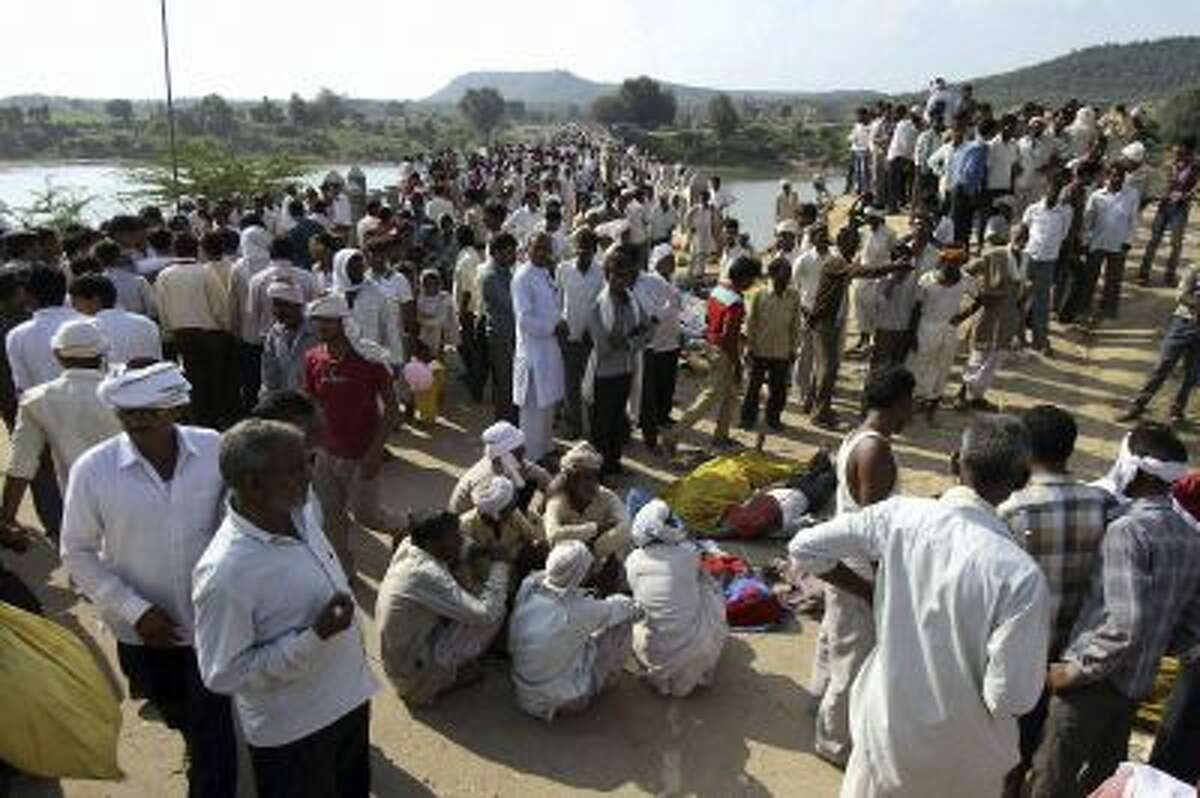 Indian villagers gather after a deadly stampede on a bridge across the Sindh River in Datia district in Madhya Pradesh state, India, Sunday, Oct. 13, 2013.