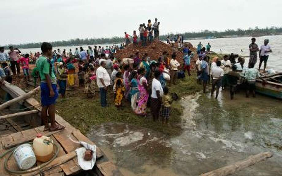 Displaced villagers wait for a boat at Sonepur village around 15kms from Gopalpur on October 13, 2013 after cyclone Phailin passed through. Photo: AFP/Getty Images / 2013 AFP