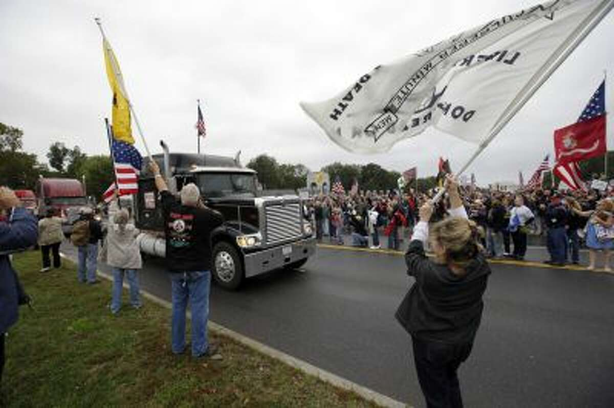 Protesters cheer as large trucks arrive at a rally at the World War II Memorial on the National Mall in Washington Sunday, Oct. 13, 2013.