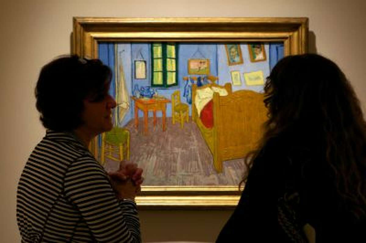 """In this Oct. 8, 2013 photo, women discuss Vincent van Gogh's """"The Bedroom at Arles,"""" on display at The Phillips Collection in Washington. (AP Photo/Molly Riley)"""