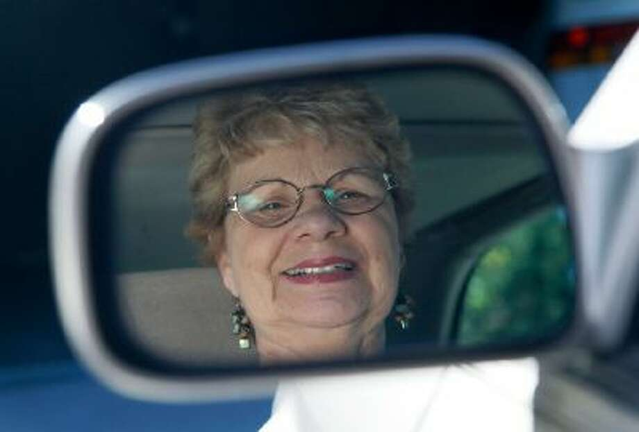 In this photo taken Sept. 12, 2012, Sandy Wiseman is reflected in the rearview mirror in Schaumburg, Ill.