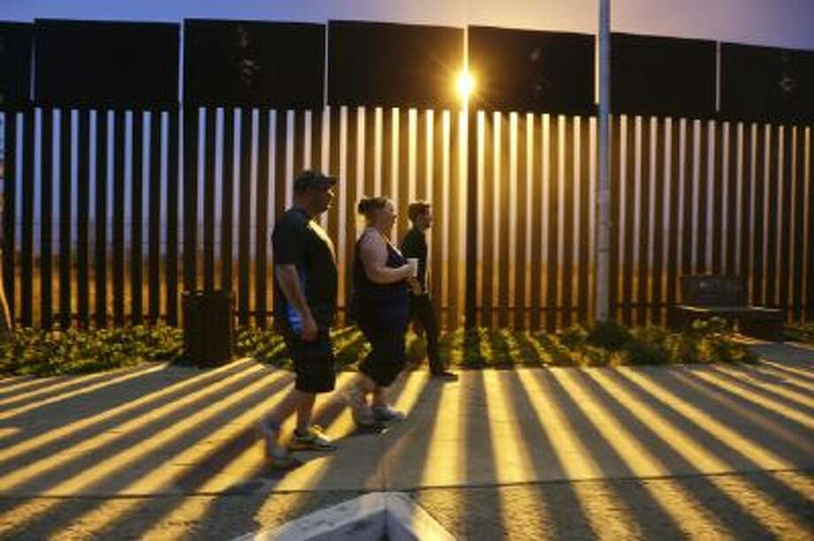 In this Nov. 15, 2013 photo, Tijuana-based tour guide Derrik Chinn, right, leads Michael Beverly and his wife Amanda, both of Newfoundland, Canada, on an evening walk along the Mexican side of the border as floodlights beam through the border structure from the United States side, in Tijuana, Mexico.