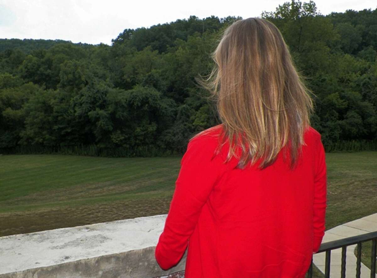 In this Aug. 22, 2013, photo, Sara, a 22-year-old client of Castlewood Treatment Center, looks over the yard at the center in St. Louis.