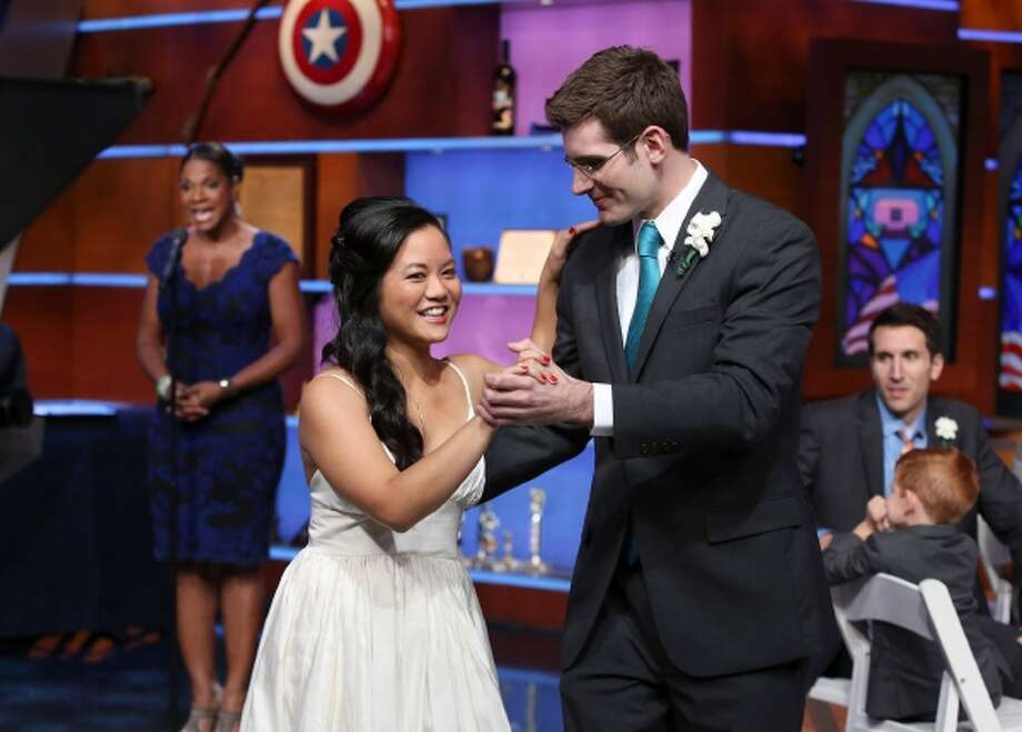 "Mike and MaiLien Cassesso, whose wedding plans were disrupted by the federal government shutdown, instead were treated to a wedding ceremony Thursday night on Comedy Central's ""The Colbert Report."" For their first dance, Audra McDonald, background, sings Billy Idol's ""White Wedding."" Photo: The Washington Post / THE WASHINGTON POST"