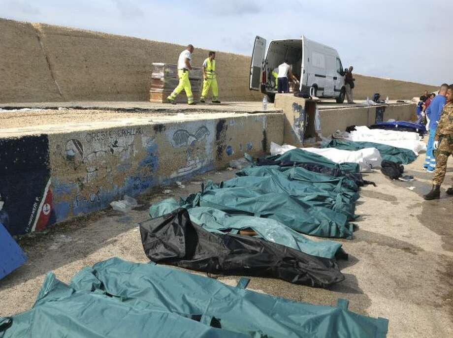 Bodies of drowned migrants are lined up in the port of Lampedusa Thursday, Oct. 3, 2013. Tens of people died when a ship carrying African migrants toward Italy caught fire and sank off the Sicilian island of Lampedusa, spilling hundreds of passengers into the sea, officials said Thursday. Many migrants have been rescued, but the boat is believed to have been carrying as many as 500 people. It is one of the deadliest migrant shipwrecks in recent times and the second one this week off... Photo: AP / Health Care Service