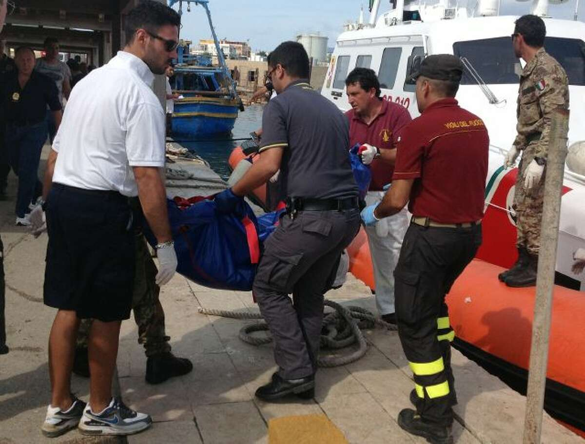 Firefighters unload the body of a drowned migrant from a Coast Guard boat in the port of Lampedusa, Sicily, Thursday, Oct. 3, 2013. Tens of people died when a ship carrying African migrants toward Italy caught fire and sank off the Sicilian island of Lampedusa, spilling hundreds of passengers into the sea, officials said Thursday. Many migrants have been rescued, but the boat is believed to have been carrying as many as 500 people. It is one of the deadliest migrant shipwrecks in recent...