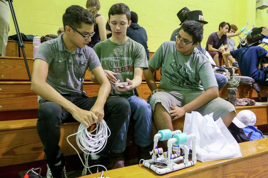 Emmanuel Corona (from left), Logan Schreier and Brandon Ochoa, all 15, prepare their underwater robot for competition during the SeaPerch Regional SeaPerch Challenge Camp Scrimmage at the Eastside Boys & Girls Club on Thursday, July, 27, 2017. Photo: Marvin Pfeiffer / San Antonio Express-News / Express-News 2017