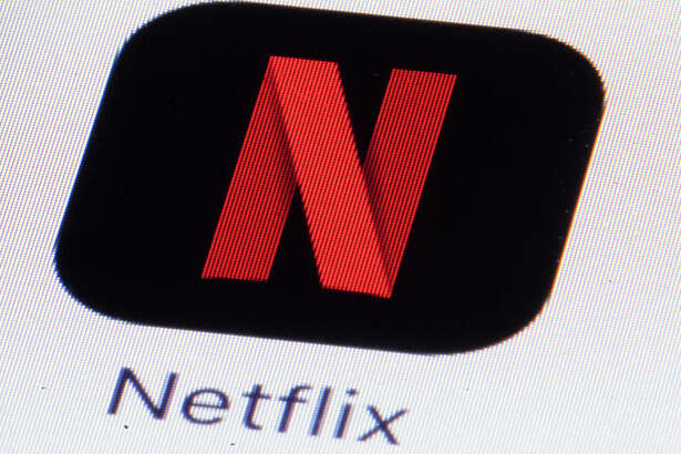 """This Monday, July 17, 2017, photo shows the Netflix logo on an iPhone in Philadelphia. Netflix says it made its first acquisition Monday, Aug. 7, 2017, buying the comic book publisher Millarworld. Millarworld's graphic novels """"Kick-Ass,"""" """"Wanted"""" and """"Kingsman"""" were all turned into movies, and Netflix plans to create more films and shows featuring Millarworld characters for its video streaming service. Netflix did not say how much it paid for Millarworld. (AP Photo/Matt Rourke)"""