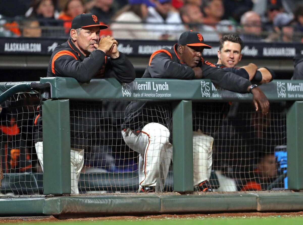 San Francisco Giants' manager Bruce Bochy, hitting coach Hensley Meulens and Buster Posey watch a game against theChicago Cubs at AT&T Park on August 7, 2017.