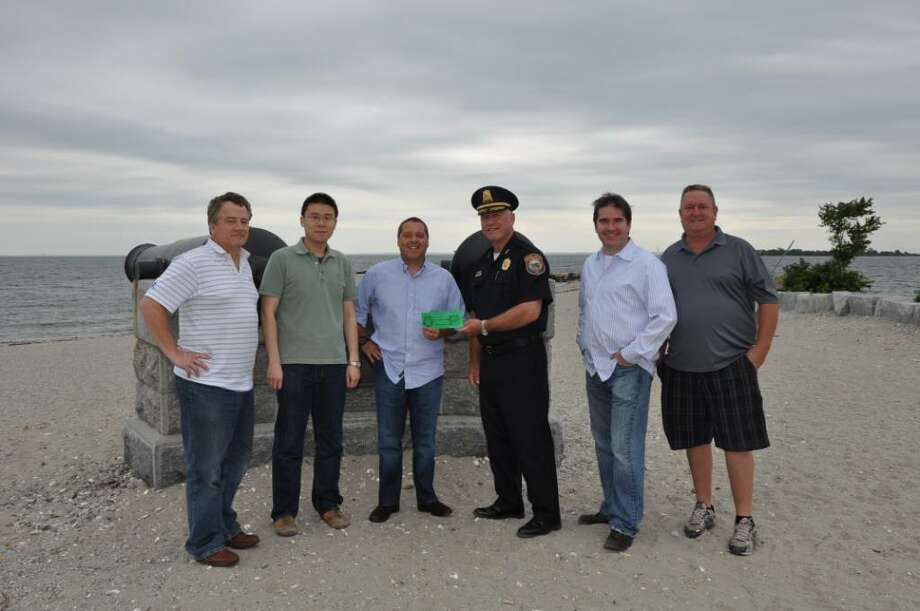 PAL President, Police Chief Al Fiore, third from right, is shown presenting ticket No. 1 to Dave Friezo, third from left, of Lydian. Also pictured from the Lydian staff, from left to right, are Jim Oakley, Bing Cui, Tom Kennedy and Scott Rochlin. Photo: Contributed Photo / Westport News