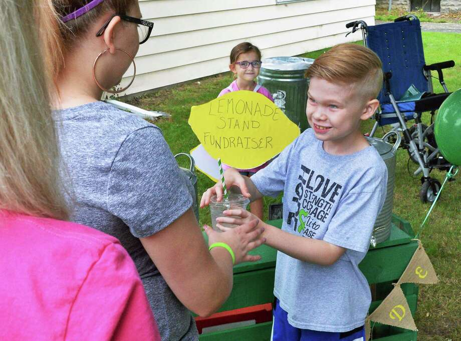 Riley LaVigne, 10, right, and his sister Ella, 5 man their fundraising lemonade and treat stand in the front yard of their home  Saturday August 5, 2017 in Albany, NY. Donations will help raise awareness and support research for finding a cure for Mitochondrial disease. (John Carl D'Annibale / Times Union) Photo: John Carl D'Annibale / 20041205A