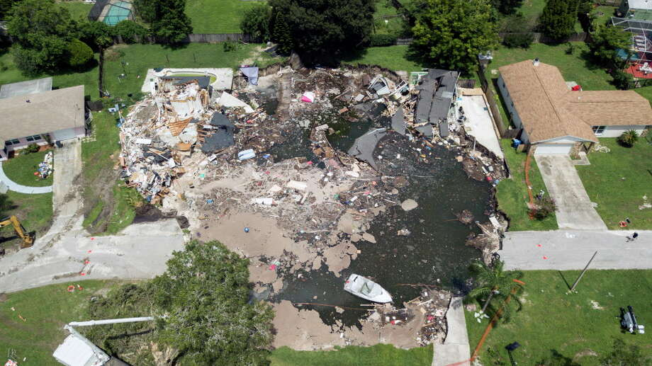 A large sinkhole in the Lake Padgett Estates community grew overnight, Friday, Aug. 4, 2017 in Land O' Lakes, Fla. Construction crews say some of the sides of the hole has collapsed making the movement of heavy machinery closer to the hole more dangerous.(Luis Santana Tampa Bay Times via AP) ORG XMIT: FLPET401 Photo: Luis Santana, AP / Tampa Bay Times