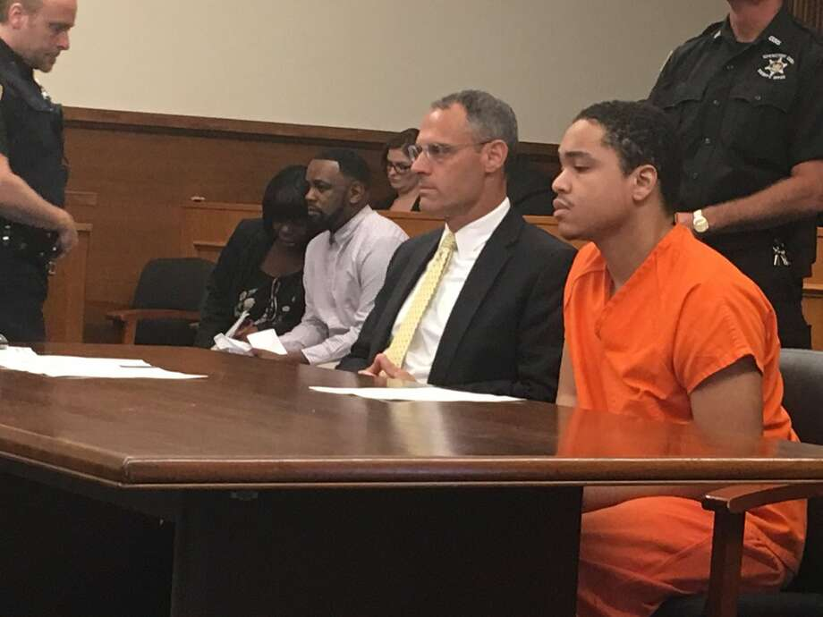 Raekwon Stover, 19, wears an orange jail  jumpsuit as he waits in Schenectady County Court to be sentenced to prison for murdering Medina Knowles, a 17-year-old he shot and killed after she told him she wanted to quit working as a prostitute for him. Stover's attorney, Adam Parisi, sits to Stover's left. Photo: Emily Masters / Times Union