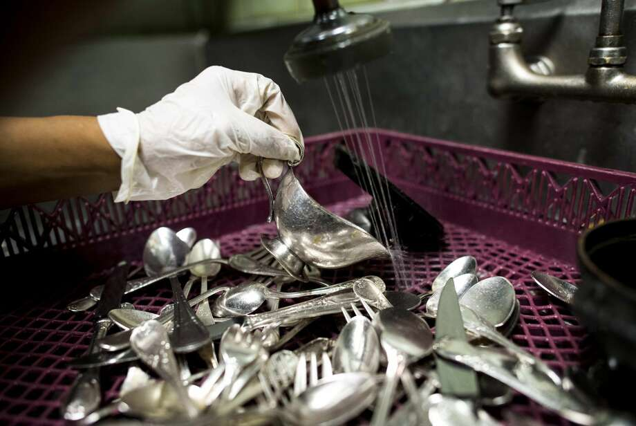 A dishwasher at Daniel, a restaurant in Manhattan, cleans silverware during dinner service. Washington Post photo by Melina Mara. Photo: Melina Mara/The Washington Post