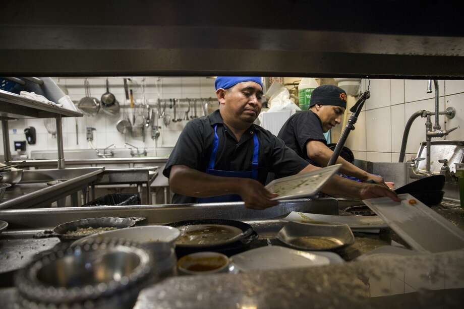 Dishwashers Esteban Soc, left, and Joselino Aguilar take turns rinsing, sorting and moving dishes through the conveyor-type machine, and then sorting them on a steel table at Caracol in Houston, on July 12, 2017. photo for The Washington Post by Scott Dalton. Photo: Scott Dalton /For The Washington Post