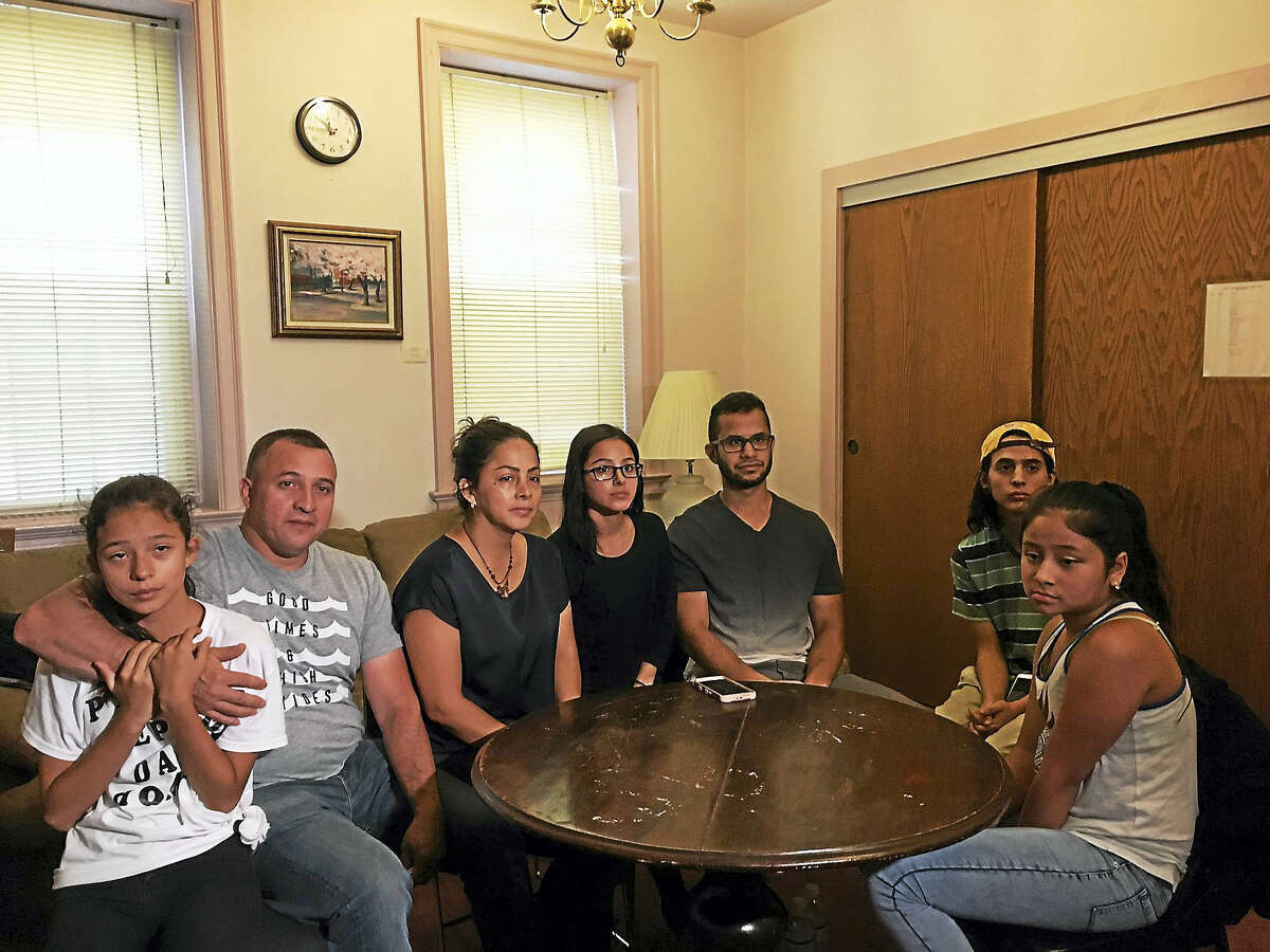 Marco Reyes Alvarez, second from left, with his family inside First and Summerfield United Methodist Church on Tuesday morning. His wife, Fanny Torres Reyes, is to his right and his daughter, Adriana, 12, is on his left. Evelyn Reyes, 23, is next to her mother. To her right is Brian Rodriguez, Evelyn Reyes' husband. Her brother Anthony Reyes, 21, is next to Rodriguez. An unidentified cousin is at the end of the seating.