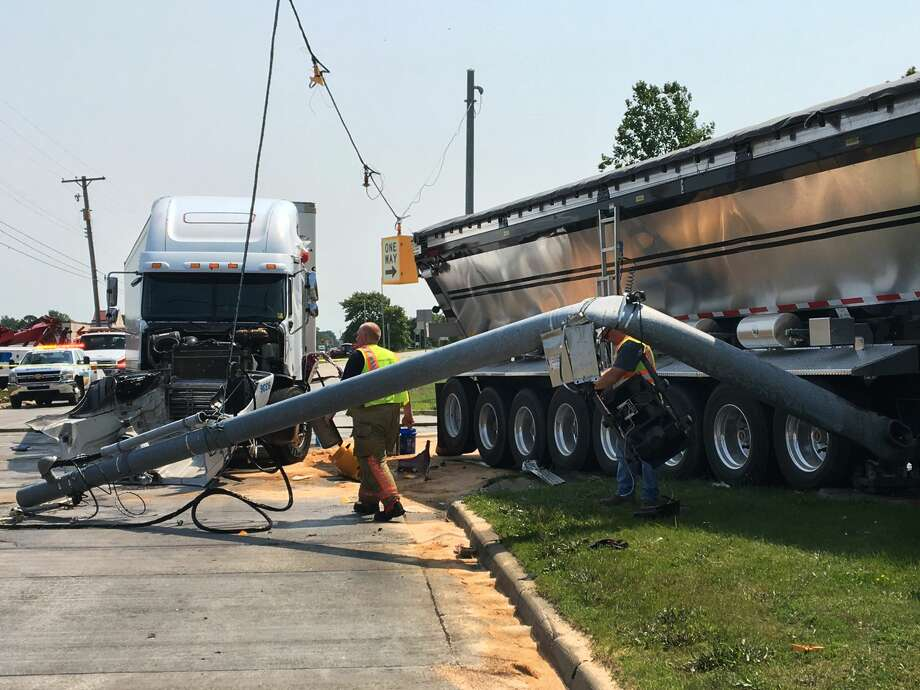 A downed traffic pole lies on the ground near two tractor-trailers after they collided while driving northbound on Washington Street, causing one to knock down the traffic light, at the intersection of Washington and Patrick on Tuesday. Photo: (Katy Kildee/kkildee@mdn.net)
