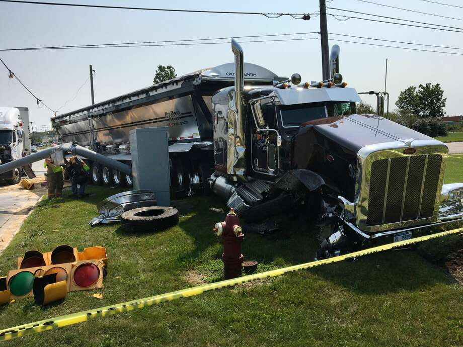 A downed traffic light lies on the ground near two tractor-trailers after they collided while driving northbound on Washington Street, causing one to knock down the traffic light, at the intersection of Washington and Patrick on Tuesday. Photo: (Katy Kildee/kkildee@mdn.net)