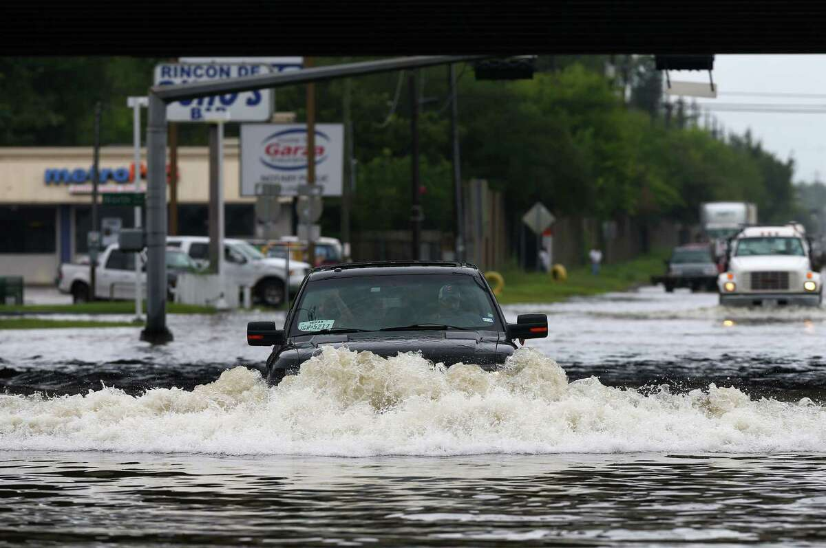 A motorist drives through the high water on West Mount Houston Road near I-45 Tuesday, Aug. 8, 2017, in Houston.