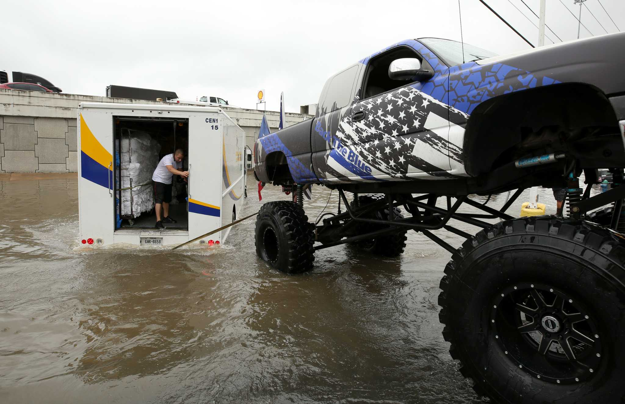 Video posted to Facebook shows a monster truck -- comprised on an SUV on monster truck wheels -- pulling a U.S. Army vehicle out of deep floodwaters in Houston on Wednesday. A crowd cheers as the.
