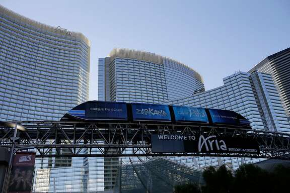 In this Thursday, Aug. 14, 2014 photo, a tram travels by the front of the Aria Resort & Casino, in Las Vegas. This year, hotels will take in a record $2.25 billion in revenue from fees and surcharges, 6 percent more than in 2013 and nearly double that of a decade ago, according to a new study. Nearly half of the increase can be attributed to new surcharges and hotels increasing the amounts of existing fees. (AP Photo/John Locher)