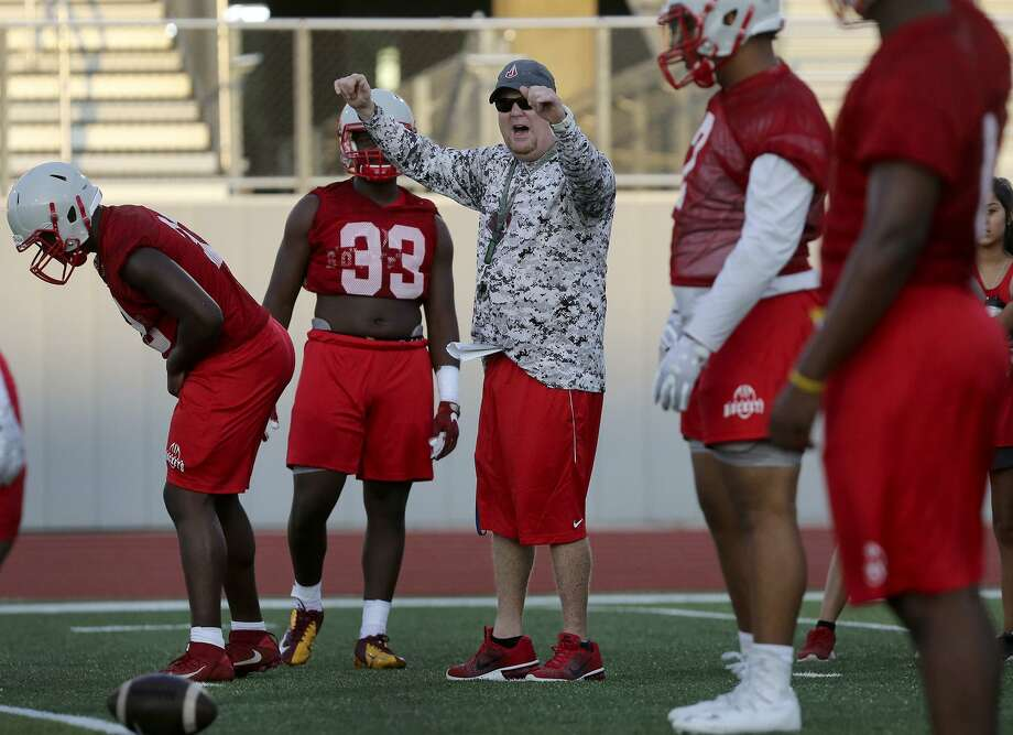 Judson coach Sean McAuliffe (center, arms raised) directs practice on Aug. 8, 2017, at Rutledge Stadium. Tuesday was the team's first workout on the field since Monday's heavy rain. Photo: John Davenport /San Antonio Express-News / ©John Davenport/San Antonio Express-News