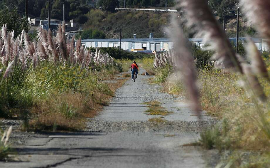 A bicyclist rides on open space land in Brisbane, CA, near Highway 101. Developers are struggling to get approval for a mixed-use project, including housing, on this land. Photo: Paul Chinn, The Chronicle