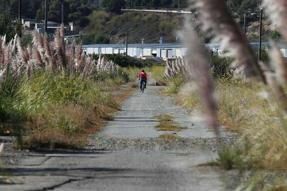 A bicyclist rides on open space land in Brisbane, CA, near Highway 101. Developers are struggling to get approval for a mixed-use project, including housing, on this land.