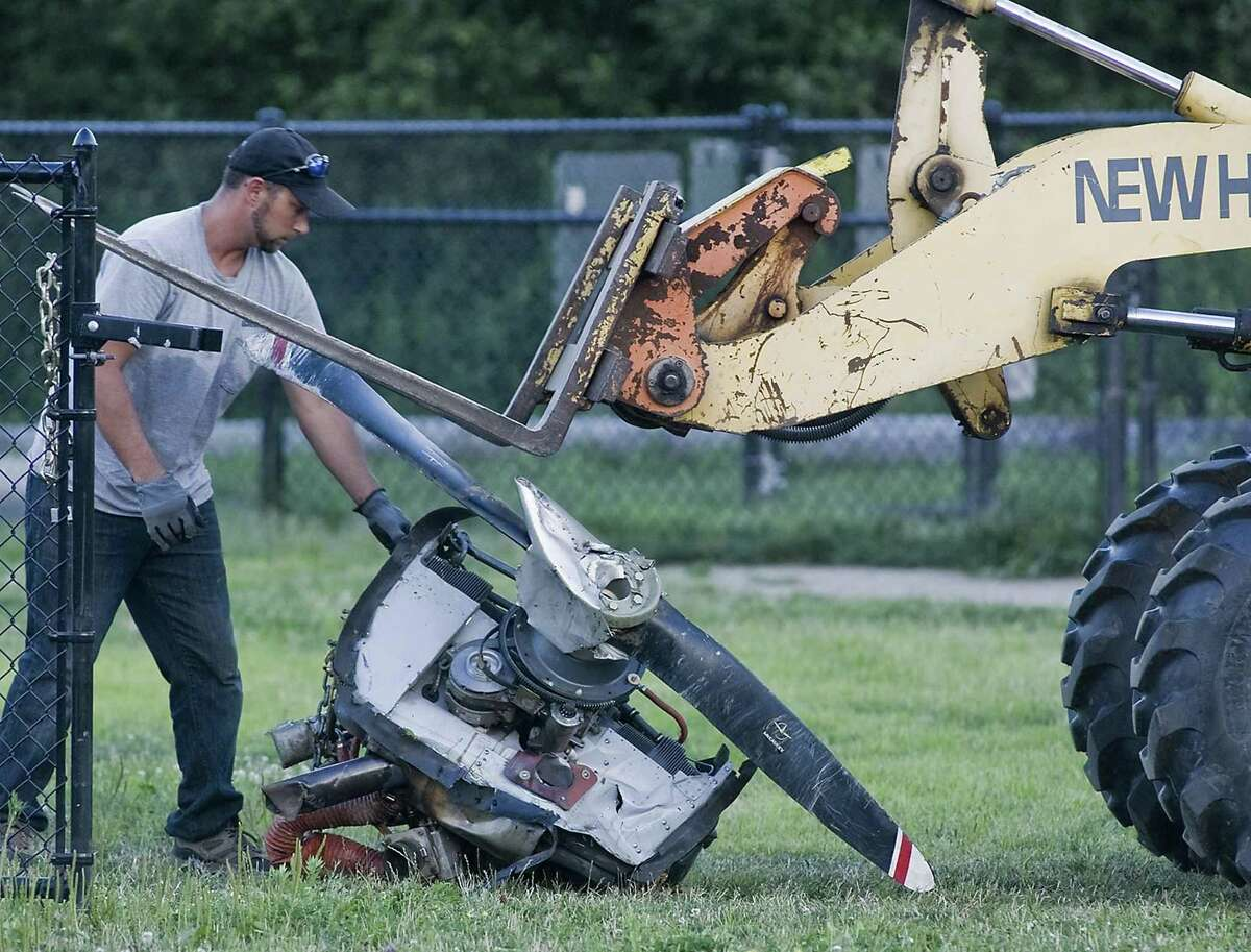 A worker removes the engine of the plane at the crash site on the west side of Danbury Airport. Monday, July 31, 2017
