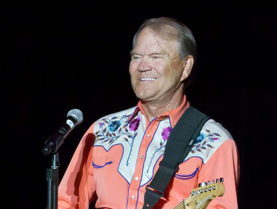 "FILE - This Sept. 6, 2012 file photo shows singer Glen Campbell performing during his Goodbye Tour in Little Rock, Ark. Campbell, the grinning, high-pitched entertainer who had such hits as ""Rhinestone Cowboy"" and spanned country, pop, television and movies, died Tuesday, Aug. 8, 2017. He was 81. Campbell announced in June 2011 that he had been diagnosed with Alzheimer's disease. (AP Photo/Danny Johnston, File) Photo: Danny Johnston, STF / Copyright 2017 The Associated Press. All rights reserved."