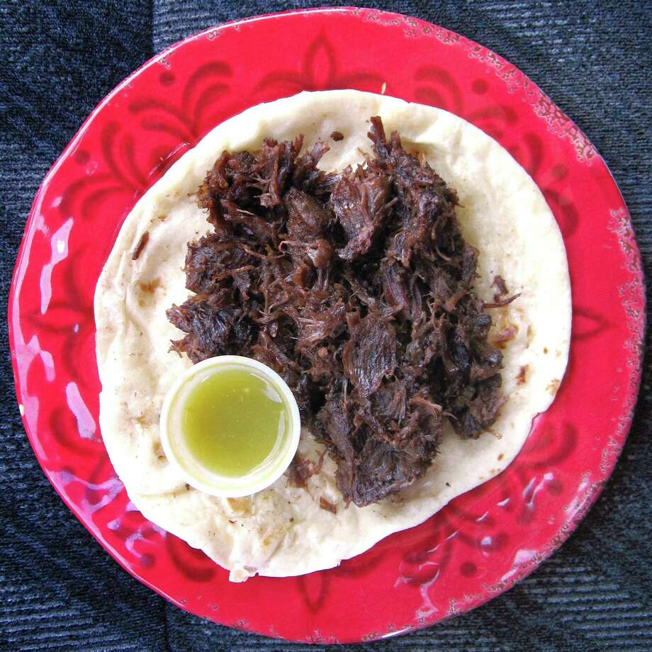 Barbacoa taco on a flour tortilla with a side of salsa verde from Ybarra's Molino. Photo: Mike Sutter /San Antonio Express-News
