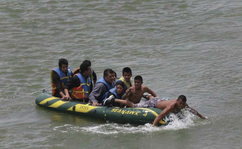 JUNE 24, 2014, 2:02 PM, ROMA, TEXAS - Using an inflatable raft, coyotes, or smugglers, carry immigrants across by the international bridge on the Rio Grande in Roma, Texas. According to law enforcement officials, higher risk smuggling operations have moved into Starr County in order to avoid the saturated border in Hidalgo, County. Photo: Jerry Lara, Staff / San Antonio Express-News / ©2014 San Antonio Express-News