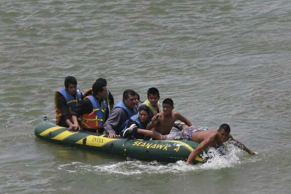 JUNE 24, 2014, 2:02 PM, ROMA, TEXAS - Using an inflatable raft, coyotes, or smugglers, carry immigrants across by the international bridge on the Rio Grande in Roma, Texas. According to law enforcement officials, higher risk smuggling operations have moved into Starr County in order to avoid the saturated border in Hidalgo, County.