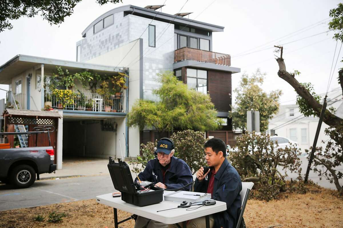 (l-r) Auxillery Communication Service (ACS) Chief Lawrence Lin (right) talks over the radio as a member of the public describes the sound of the sirens they were hearing in San Francisco, Calif., on Tuesday, Aug. 8, 2017. Volunteer Peter McElmury (left) and Chief of ACS Lawrence Lin take calls from members of the public who listen to the weekly siren alert system and call in to describe its effectiveness.