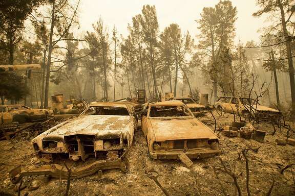 FILE - In this Sept. 28, 2016, file photo, vintage cars line a property after the Loma fire burned through Loma Chiquita Road near Morgan Hill, Calif. As President Donald Trump touts new oil pipelines and pledges to revive the nation�s struggling coal mines, federal scientists are warning that burning fossil fuels is already driving a steep increase in the United States of heat waves, droughts and floods. (AP Photo/Noah Berger, File)