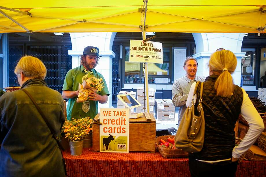 Justin Outten, right, and Kenny Baker, left, ring out customers at  Lonely Mountain Farm stand during the Ferry Plaza Farmer's Market. Photo: Nicole Boliaux, The Chronicle