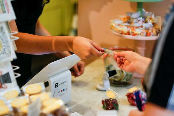 Katie Jackson  accepts a customer's credit card during a transaction during the Ferry Plaza Farmer's Market at the Ferry Building in San Francisco on Friday, August 4, 2017.