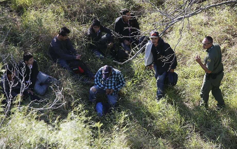 With the support of a U.S. Customs and Border Protection Air and Marine Operations Bell Huey, Border Patrol agents capture a group illegal immigrant hiding in brush on a ranch northeast of Rio Grande City, Texas, Tuesday, Oct. 4, 2016. Photo: JERRY LARA, San Antonio Express-News