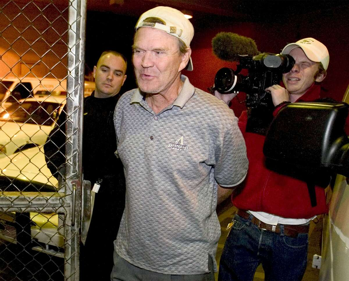 Country singer Glen Campbell arrives in handcuffs at the Madison Street Jail in Phoenix, Monday, Nov. 24, 2003. Campbell was taken into custody Monday on suspicion of drunken driving after he left the scene of a minor vehicle accident, police said. Campbell was also being held on suspicion of hit and run, and aggravated assault on a police officer. Phoenix police Sgt. Randy Force said that as Campbell was being processed at the police station, he kneed a sergeant in the thigh. (AP Photo/Arizona Republic, Dave Cruz) ** MANDATORY CREDIT **