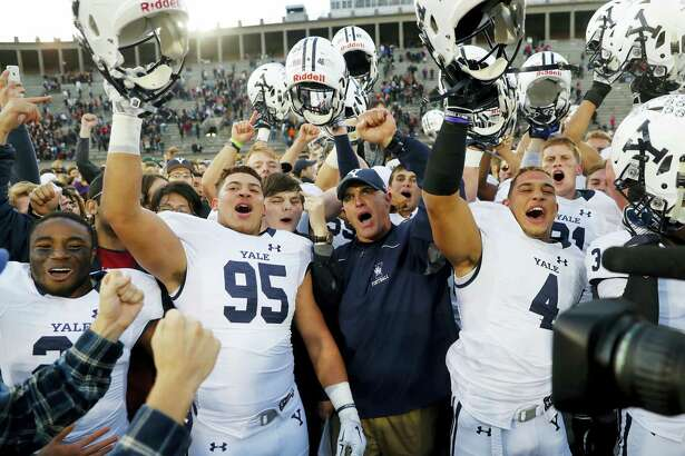 Yale head coach Tony Reno, center, celebrates with his team after their 21-14 win over Harvard in Cambridge, Mass. last November. The Bulldogs are picked to finish fourth in the Ivy League this season.