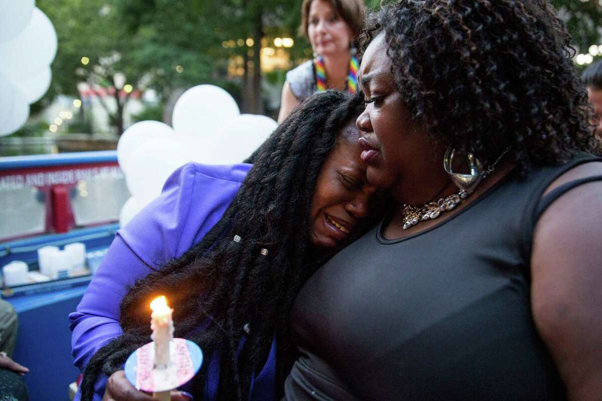 Telina Kuykendall is comforted by her mother Joann McFadden during a Tuesday vigil for her younger sibling Kenne McFadden, a trans woman who was found dead in the River Walk.