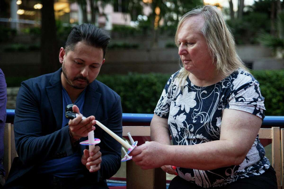 Julian Tovar and Lauryn Farris light candles during a vigil for Kenne McFadden, a trans woman who was found dead in April. Tuesday would have been her 27th birthday.